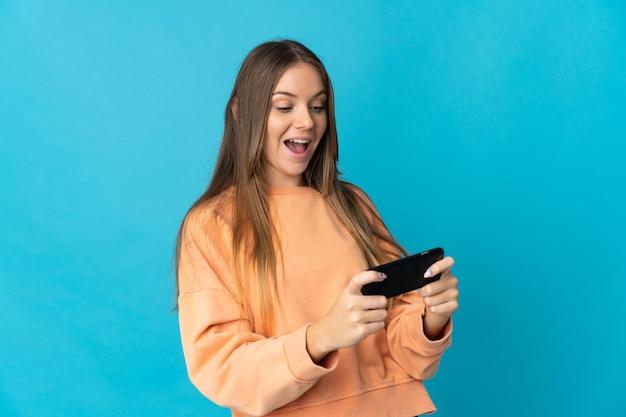 Młoda litewska kobieta na białym tle na niebieskim tle gry z telefonem komórkowym