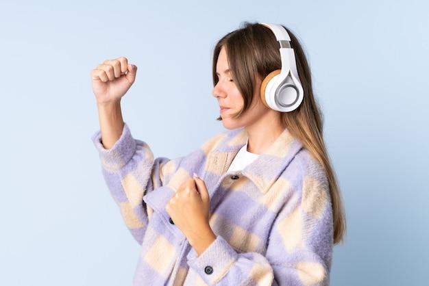 Młoda litewska kobieta na białym tle na niebieskim tle słuchania muzyki i tańca