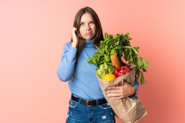 Młoda litewska kobieta sfrustrowana i zakrywająca uszy trzymająca torbę na zakupy spożywcze