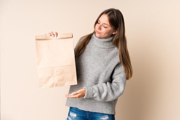 Młoda litewska kobieta trzyma torbę na zakupy spożywcze ze smutnym wyrazem twarzy