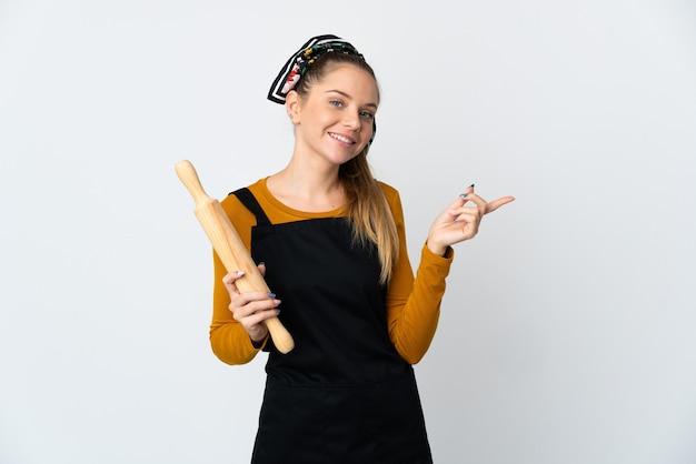 Młoda litewska kobieta trzyma wałek do ciasta na białym tle na białej ścianie palcem wskazującym w bok