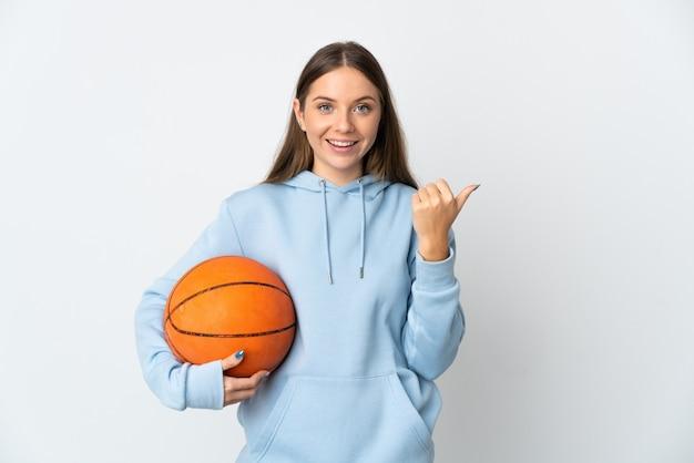 Młoda litwinka gra w koszykówkę na białym tle, wskazując na bok, aby zaprezentować produkt