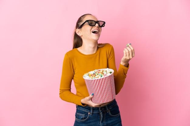 Młoda litwinka na białym tle na różowym tle w okularach 3d i trzyma duże wiadro popcorns