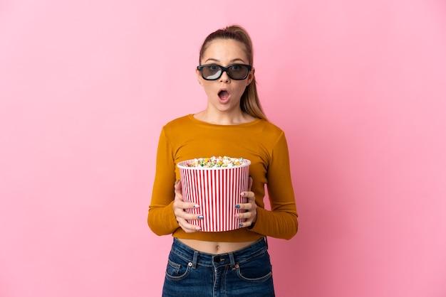 Młoda litwinka na białym tle na różowym tle zaskoczona okularami 3d i trzyma duże wiadro popcornu