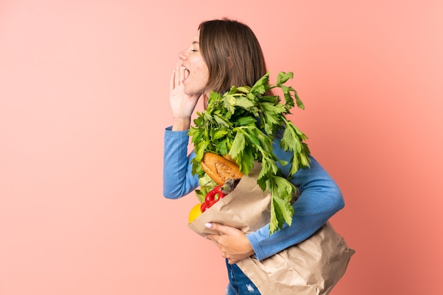 Młoda litwinka trzyma torbę na zakupy, krzycząc z szeroko otwartymi ustami
