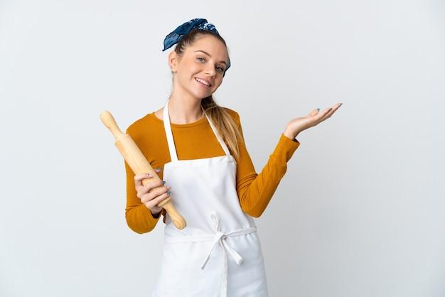 Młoda litwinka trzyma wałek do ciasta na białym tle na białej ścianie, wyciągając ręce na bok, by zaprosić do przyjścia