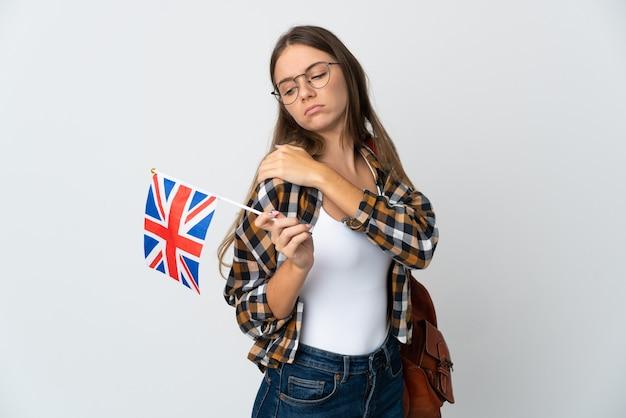 Młoda litwinka trzymająca flagę wielkiej brytanii na białym tle cierpi na ból w ramieniu za wysiłek having