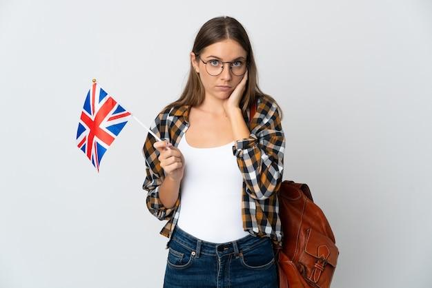 Młoda litwinka trzymająca flagę wielkiej brytanii na białym tle sfrustrowana i zakrywająca uszy