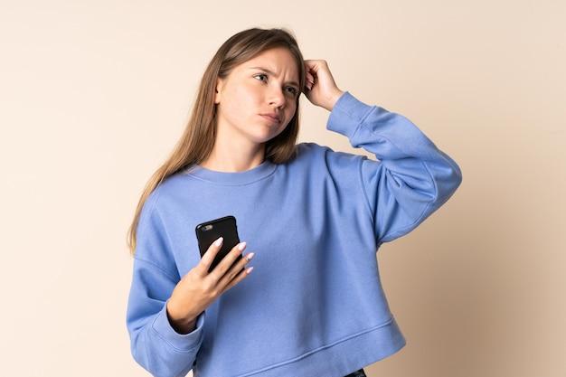 Młoda litwinka używa telefonu komórkowego na beżowym tle i ma wątpliwości iz niejasnym wyrazem twarzy