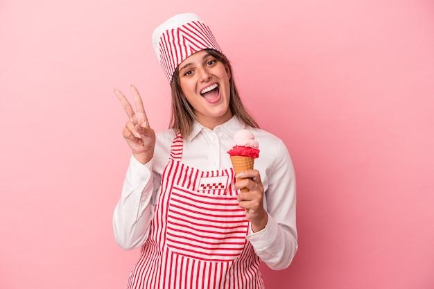 Młoda lody kobieta trzyma lody na białym tle na różowym tle radosna i beztroska pokazując symbol pokoju palcami.