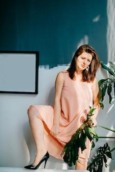 Młoda łup seksowna laska w różowej koszuli nocnej pozuje do kamery. niesamowita dziarska niegrzeczna dziewczyna w peignoir pozuje w wewnętrznym pokoju
