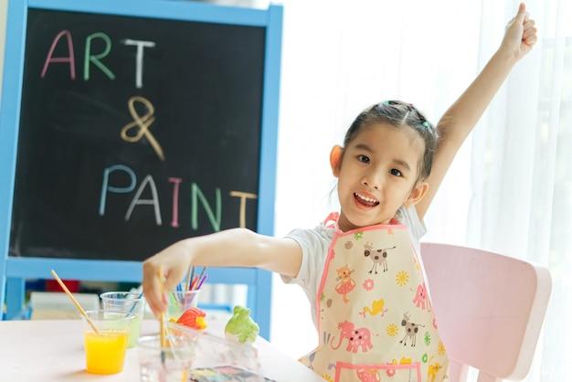 Młoda mała azjatycka dziewczyna maluje tynk lale w obraz klasie