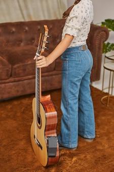 Młoda mała dziewczynka gra na gitarze w domu