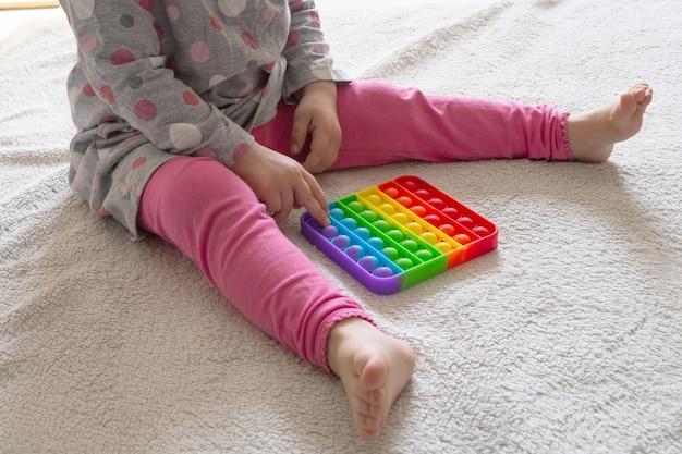 Młoda mała dziewczynka siedzi na dywanie w domu i bawi się nową modną zabawką pop it