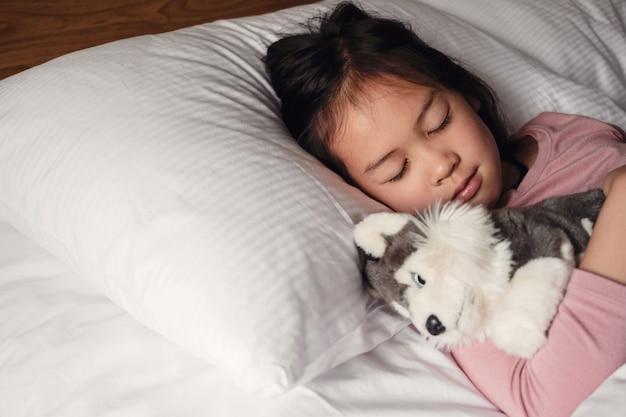 Młoda mała mieszana rasa azjatycka dziewczyna śpi w łóżku z psem, pluszową zabawką, rutyną na dobranoc, budzenie dziecka do szkoły, zaburzenia snu u dzieci