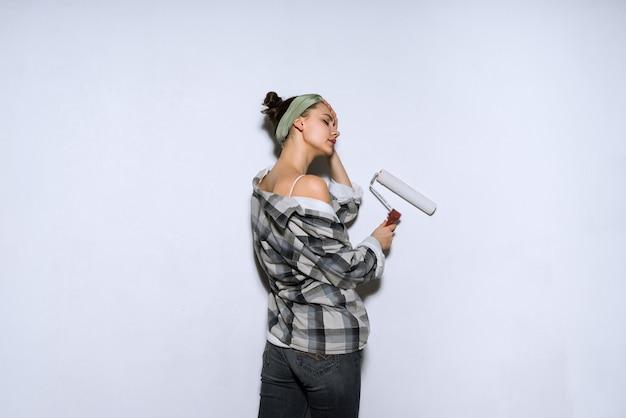 Młoda malarka w kraciastej koszuli koloruje ścianę za pomocą białego wałka, naprawa w nowym mieszkaniu
