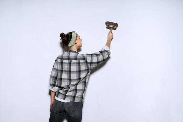 Młoda malarka w kraciastej koszuli maluje pędzlem ściennym, naprawa w nowym mieszkaniu