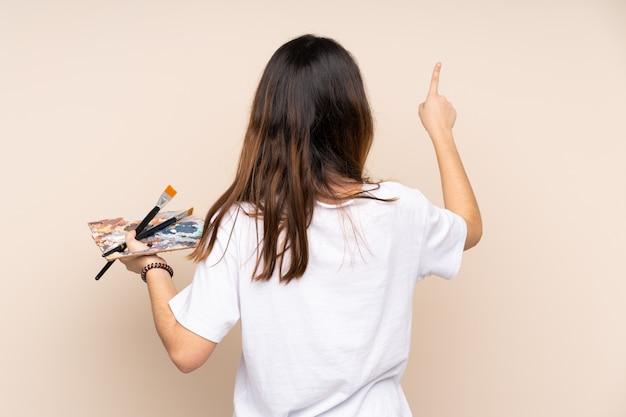 Młoda malarz kobieta nad odosobnioną ścianą