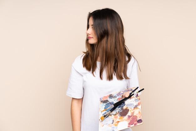 Młoda malarz kobieta nad odosobnionym tłem