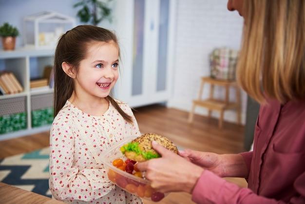Młoda mama daje córce zdrową kanapkę