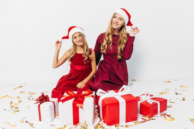Młoda mama i córka w czapkach mikołaja zabawy z prezentami świątecznymi