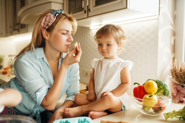 Młoda mama i dziecko smakują świeże ciasto czekoladowe.