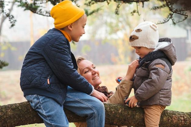 Młoda mama i jej synowie świetnie się bawią na świeżym powietrzu. moda zimowa. szczęśliwa rodzina bawić się outdoors przy zimną pogodą. pojęcie rodziny, macierzyństwa, ludzi i mody
