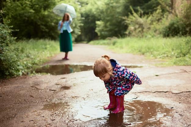 Młoda mama i mała córka bawią się spacery w gumboots na baseny w parku