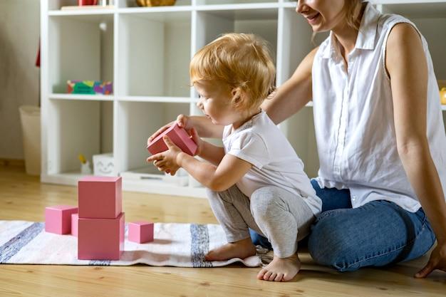 Młoda mama i małe dziecko montują ekologiczne materiały w różowej kostce maria montessori