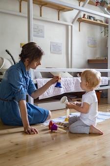 Młoda mama i mały maluch grają w domu dziecinne kolorowe dzwonki ręczne
