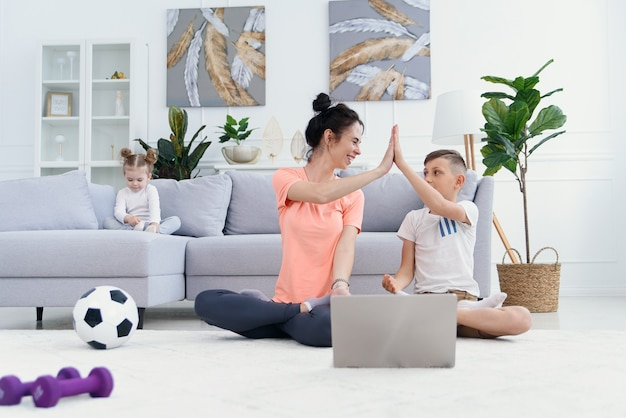 Młoda mama i syn ćwiczą jogę z laptopem na podłodze w domu.