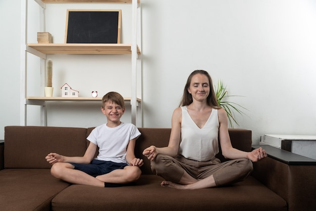 Młoda mama i syn uprawiają jogę w domu. mama i dziecko siedzą w pozycji lotosu i medytują.