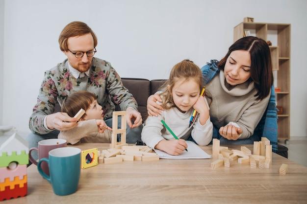 Młoda mama i tata grają w gry edukacyjne z dziećmi