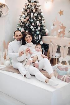 Młoda mama i tata z dzieckiem w białych ubraniach, siedząc razem