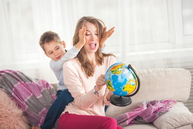Młoda mama pomaga synowi odrabiać lekcje. rodzina wybiera, gdzie podróżować na wakacjach. matka i jej dziecko trzyma kulę ziemską