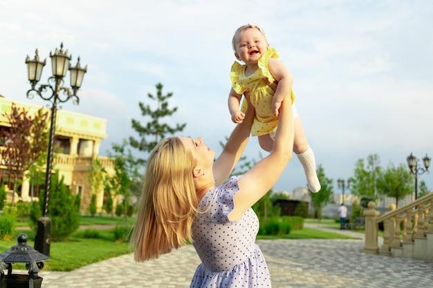 Młoda mama spaceruje latem z dzieckiem w parku, rzuca je, szczęśliwe macierzyństwo