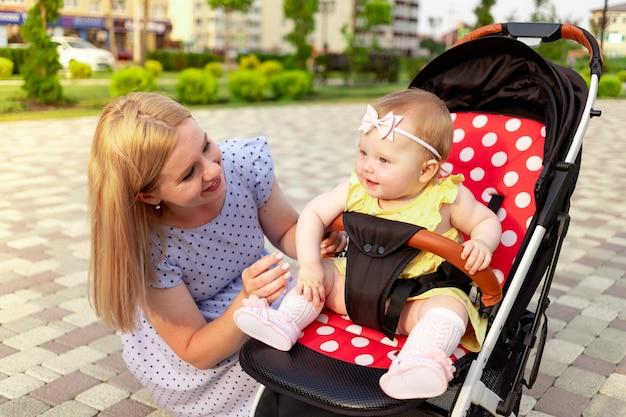Młoda mama spaceruje latem z dzieckiem w wózku w parku rozmawiając lub bawiąc się z nim, szczęśliwe macierzyństwo