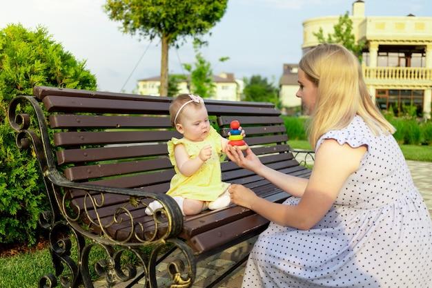 Młoda mama spaceruje z dzieckiem latem po parku, siedząc na ławce i bawiąc się w piramidę, szczęśliwe macierzyństwo