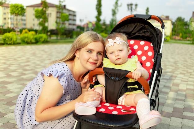 Młoda mama spaceruje z dzieckiem w wózku latem w parku, szczęśliwe macierzyństwo