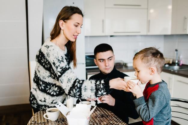 Młoda mama, tata i chłopiec piją kawę i herbatę rano. rodzina spożywająca śniadanie w kuchni.