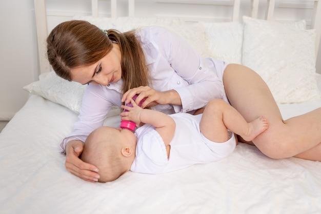 Młoda mama trzyma w ramionach sześciomiesięczne dziecko i karmi je mlekiem z butelki na białym łóżku, miłość matki i dziecka, dzień matki