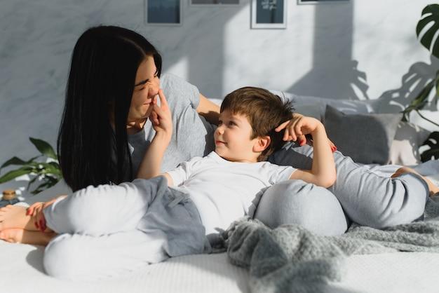 Młoda mama z 4-letnim synkiem ubrana w piżamę odpoczywa i bawi się w łóżku