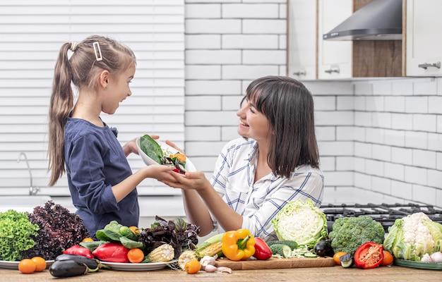 Młoda mama z córką z wieloma warzywami na przestrzeni wnętrza nowoczesnej jasnej kuchni.