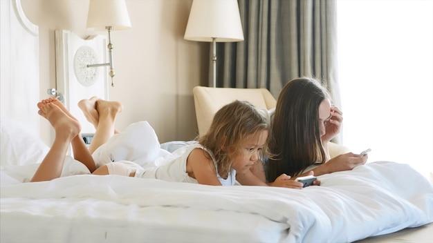 Młoda mama z małą uroczą córeczką używa gadżetów leżących na białym łóżku.