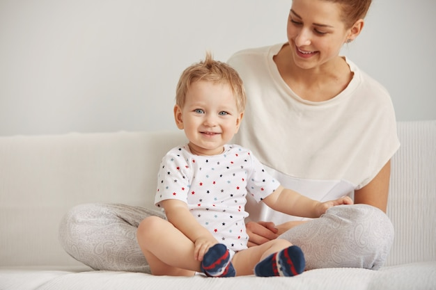 Młoda mama z rocznym synkiem ubrana w piżamę odpoczywa