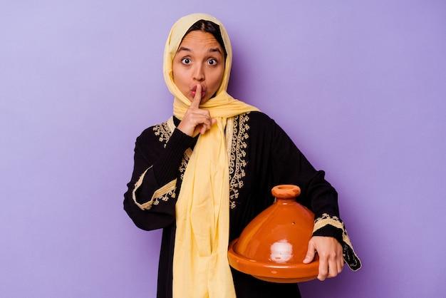 Młoda marokanka trzymająca tajine na fioletowej ścianie trzymająca tajemnicę lub prosząca o ciszę.