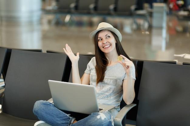 Młoda marzycielska podróżniczka turystyczna kobieta w kapeluszu siedząca, pracująca na laptopie, trzymająca bitcoina, rozkładająca ręce, czekająca w holu na lotnisku