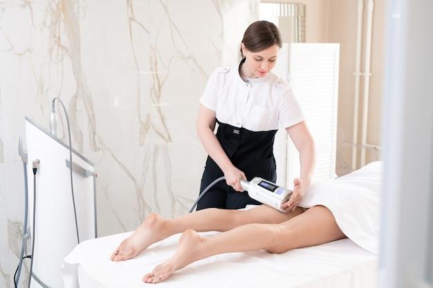 Młoda masażystka robi kobiecie masaż ciała lpg, aby wyszczuplić ją w salonie piękności