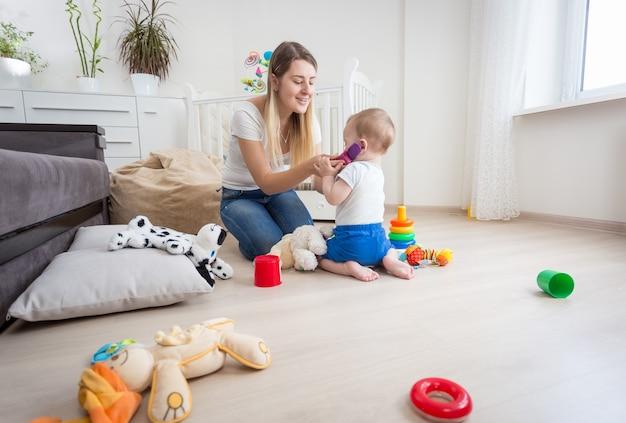 Młoda matka bawi się swojego synka i udaje, że rozmawia przez telefon