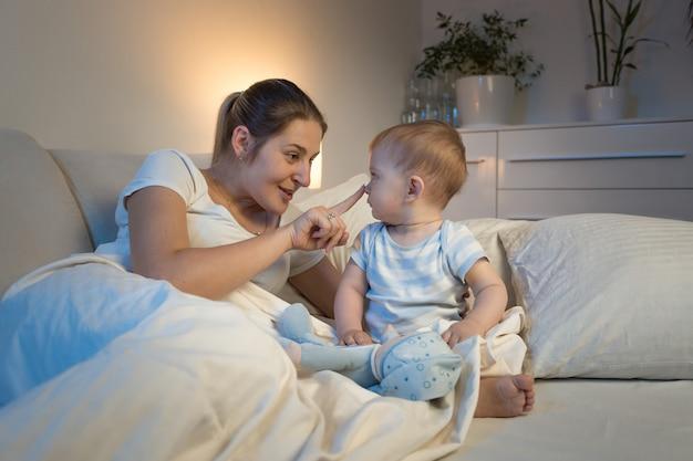 Młoda matka bawi się z synkiem na łóżku w nocy